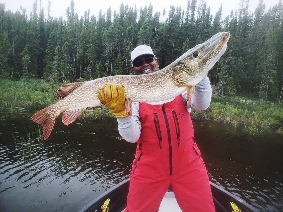A person holding a large northern pike